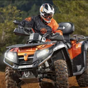 ATV with a helmeted rider, out on a trail