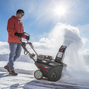 Man using a snowblower in a blue sky day
