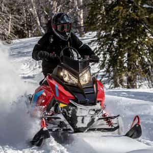 Man riding a snowmobile on a deep winter trail