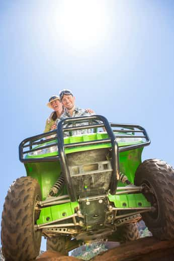 Couple sitting on a green ATV with a bright blue sky behind them