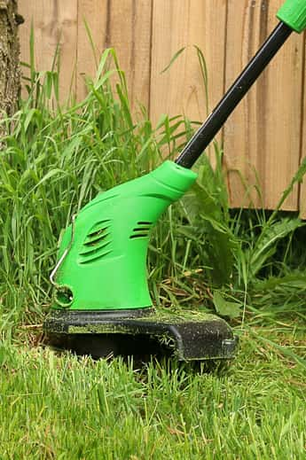 Grass trimmer being used near a fence with tall grass