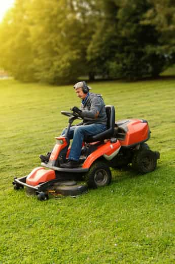 Landscaper wearing ear protection rides a lawnmower