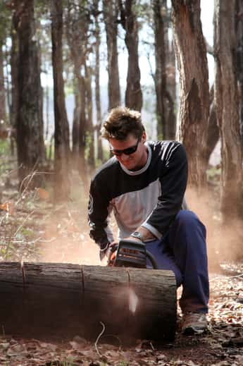 Man chopping up tree with chainsaw