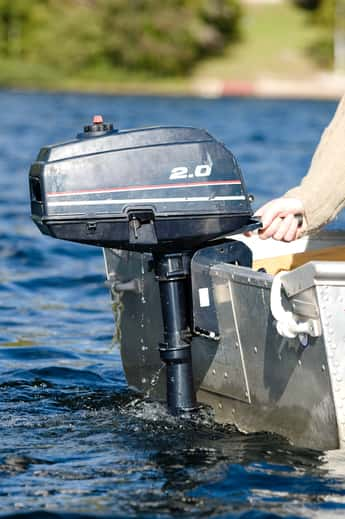 Man sitting in boat with outboard motor