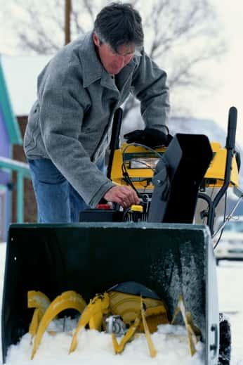 Man struggling to start broken snowblower