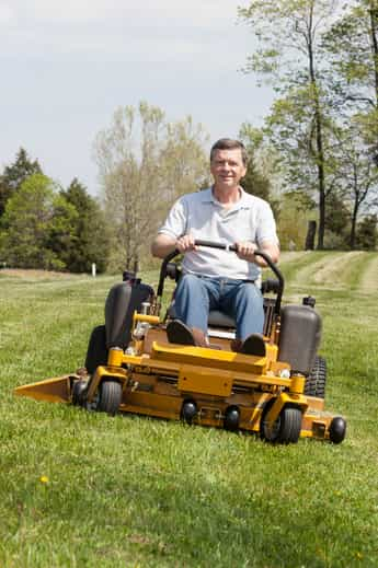 Older man riding zero-turn lawnmower