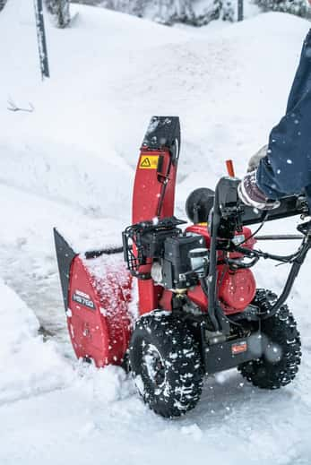 Red snowblower plower through large snowfall