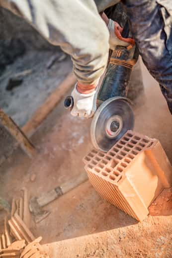 Worker cutting bricks concrete saw