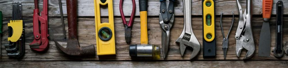 Tools lined up side by side on a wooden bench